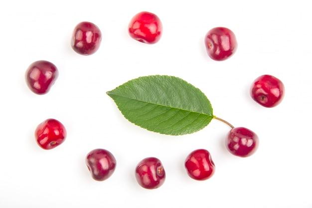 Frutta della ciliegia con la bella foglia con alta vitamina c in composizione rotonda isolata