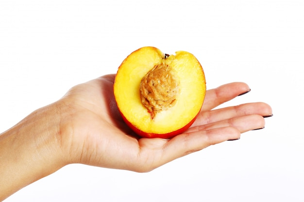 Frutta della pesca in mano della donna