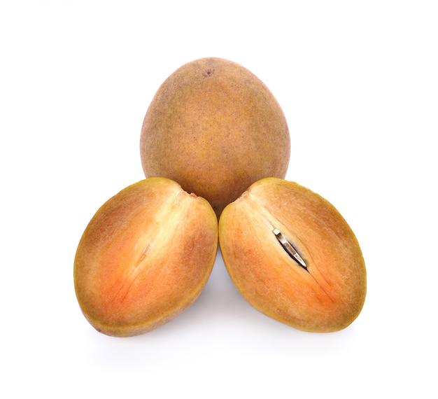 Frutta della sapota su fondo bianco.