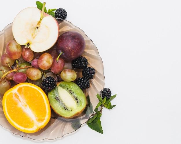 Frutta dimezzata; more e uva nella ciotola su sfondo bianco