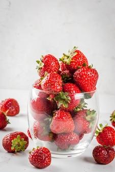 Frutta e bacche estive. fragola organica cruda fresca in bicchiere sulla tavola di marmo bianca