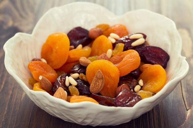 Frutta e noci asciutte in piatto bianco su superficie di legno