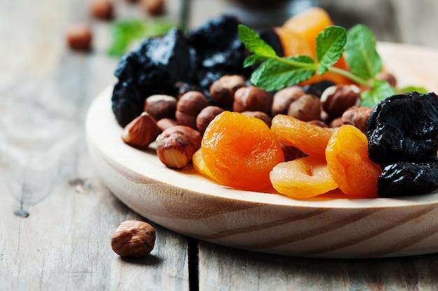 Frutta e noci secche sul piatto di legno