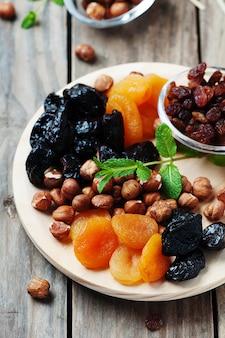 Frutta e noci secche sul vassoio di legno