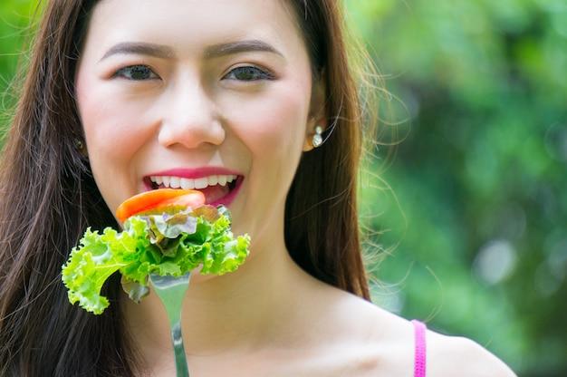 Frutta e verdura asiatiche della tenuta della donna di bellezza per sano su erba con il sorriso