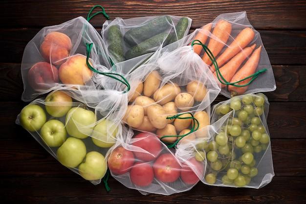 Frutta e verdura in sacchetti ecologici riutilizzabili su fondo di legno. zero sprechi.