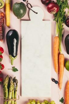 Frutta e verdura su sfondo rosa, piatto laico, vista dall'alto