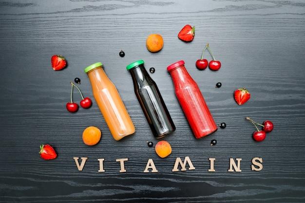 Frutta e vitamine dell'iscrizione su un fondo di legno nero. concetto di cibo