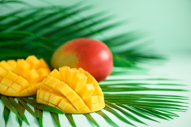 Frutta esotica del mango sopra le foglie di palma verdi tropicali. pop art design, concept creativo estivo.