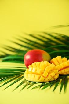 Frutta esotica del mango sopra le foglie di palma verdi tropicali su fondo giallo. pop art design, concept creativo estivo. bandiera