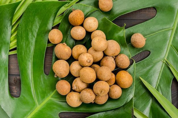 Frutta esotica longan, lam-yay o dragon's eye. diversi frutti su monstera e foglie di palma.