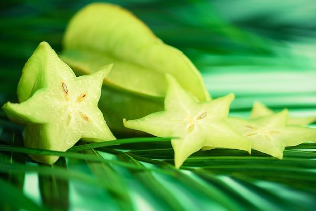 Frutta esotica stella o averrhoa carambola su foglie di palma verde tropicale su sfondo turchese.