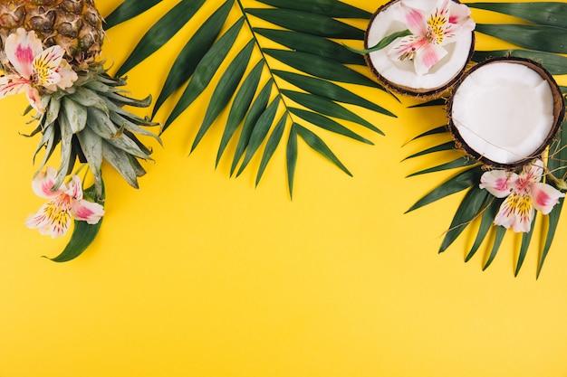 Frutta estiva foglie di palma, ananas e noce di cocco tropicali su fondo giallo.