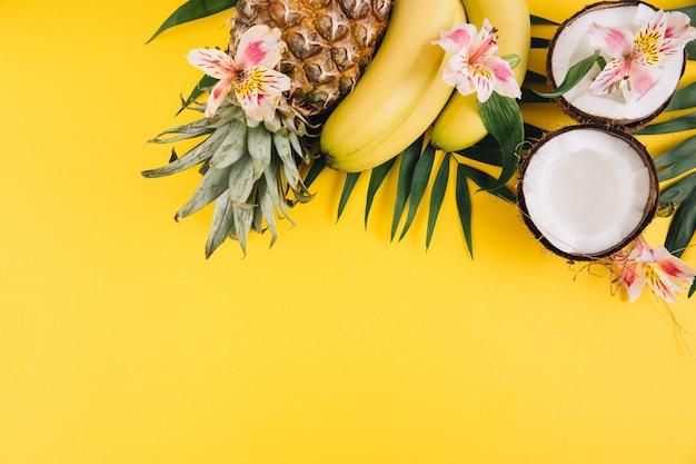 Frutta estiva foglie di palma tropicale, ananas, cocco e banane su sfondo giallo.