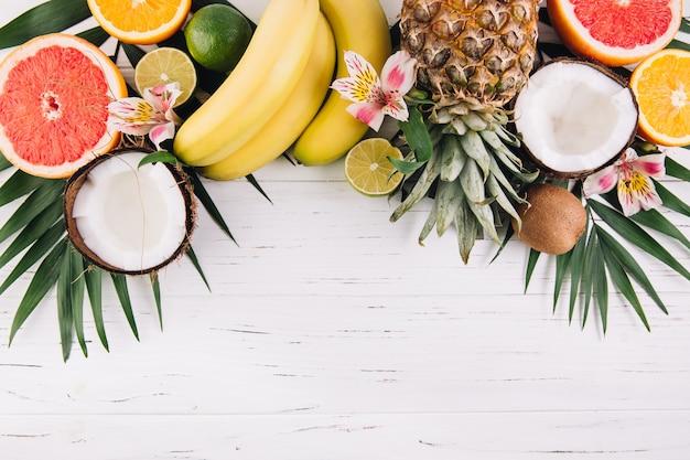 Frutta estiva foglie di palma tropicale, ananas, cocco, pompelmo, arancia e banane su fondo in legno.