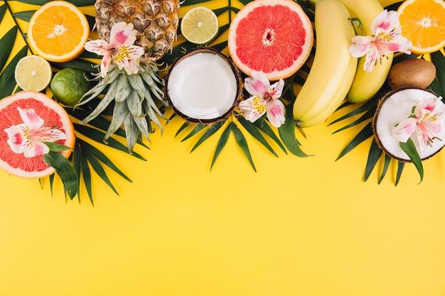 Frutta estiva foglie di palma tropicale, ananas, cocco, pompelmo, arancia e banane su sfondo rosa.