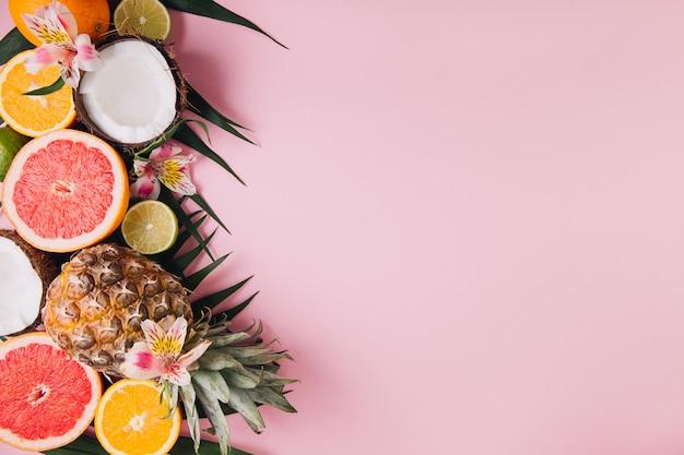 Frutta estiva foglie di palma tropicale, ananas, cocco, pompelmo, arancia e lime su sfondo rosa.