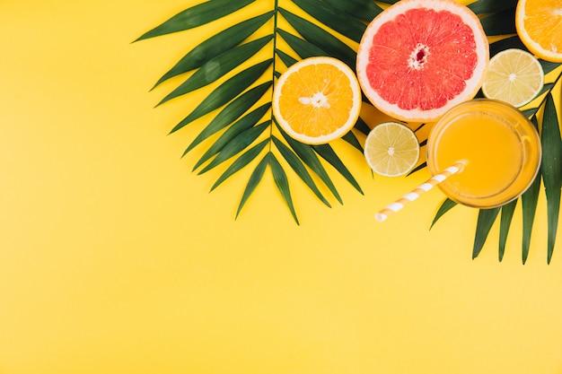 Frutta estiva foglie di palma tropicale, calce, pompelmo, arancia e bicchiere di succo su sfondo giallo.