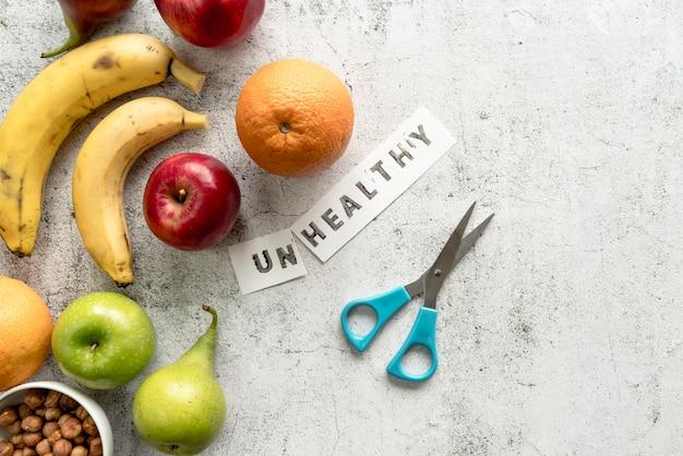 Frutta fresca con carta tagliata malsana e forbice