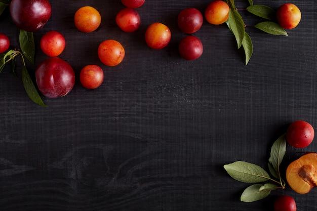 Frutta fresca con foglie su fondo rustico in legno scuro,