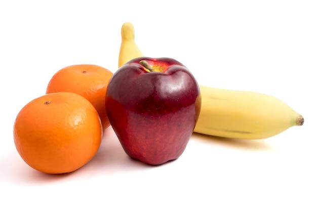Frutta fresca con mela, banana e arance su sfondo bianco.