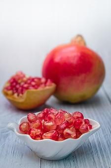 Frutta fresca del melograno su bianco di legno.