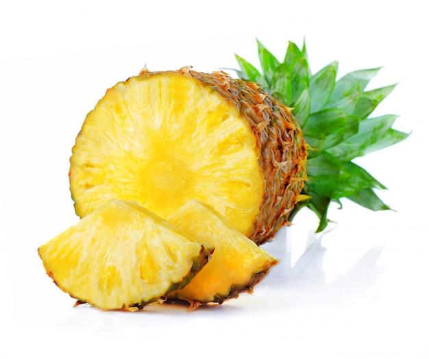 Frutta fresca dell'ananas con il taglio e foglie verdi isolate su bianco