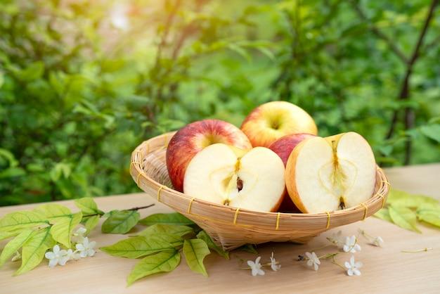 Frutta fresca di mela nel cestino di bambù sulla tavola di legno in giardino.