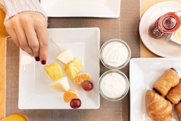 Frutta fresca di raccolto a mano della donna. colazione deliziosa vista dall'alto croissant freschi, frutta e yogurt. natura morta di dolci e frutta vista dall'alto.