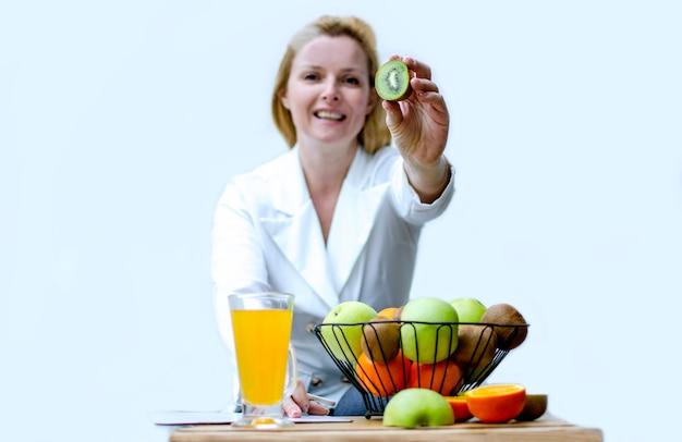 Frutta fresca e nutrizionista femminile che tengono kiwi per un'alimentazione sana vitamine per il sistema immunitario frutta e succo che si chiudono su nel posto di lavoro della donna alla clinica
