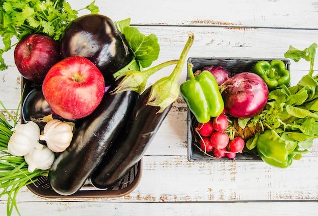 Frutta fresca; e verdure nel cestino di plastica sul tavolo di legno