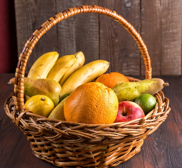 Frutta fresca in un cestino sulla tavola di legno.