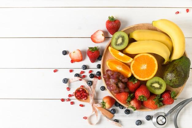 Frutta fresca nel cestino di bambù su fondo di legno bianco