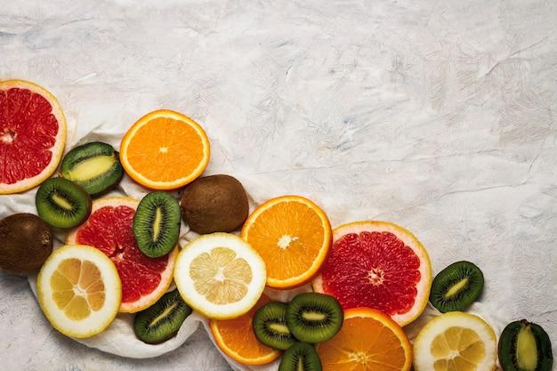 Frutta fresca, pompelmo, limone, arancia, kiwi su uno sfondo di pietra chiara.