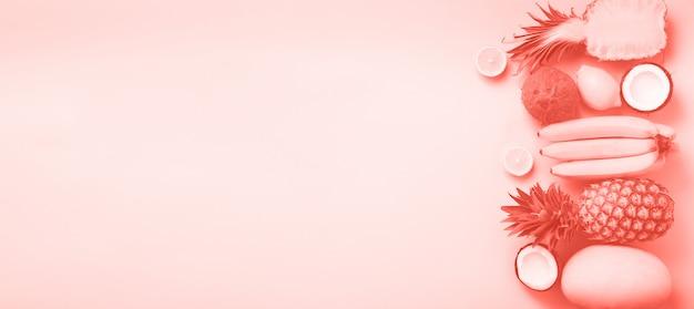 Frutta fresca su sfondo soleggiato. concetto monocromatico con banana, cocco, ananas, limone, melone in color corallo. vista dall'alto. copia spazio. design pop art, design estivo creativo.