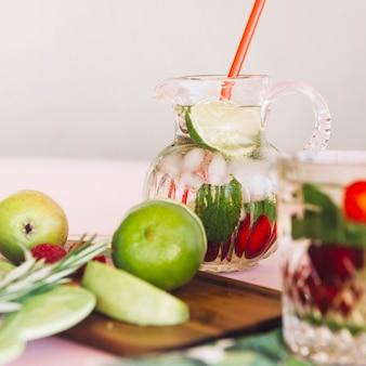 Frutta fresca sul tagliere di fronte a succo in vaso