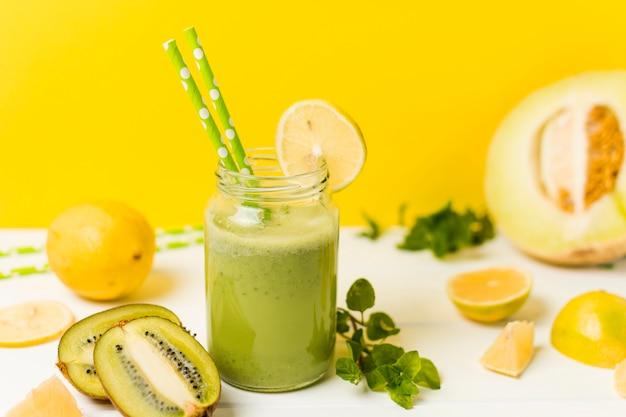 Frutta fresca vicino a erbe e vetro con cocktail