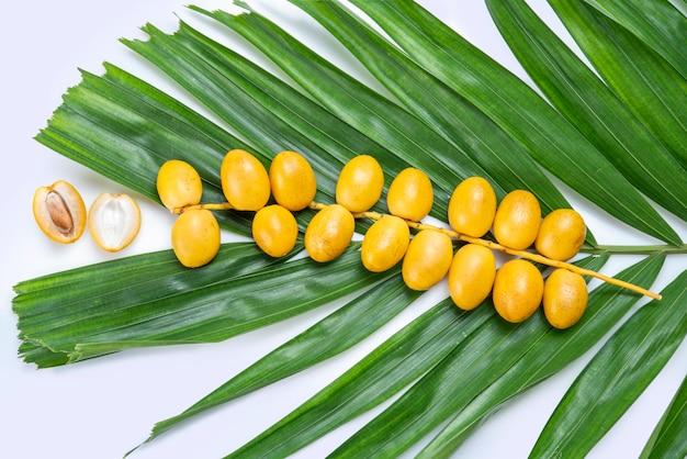 Frutta gialla della palma da datteri isolata su fondo bianco, mazzo di frutta fresca della palma da datteri con la foglia della frutta della palma da datteri su fondo bianco