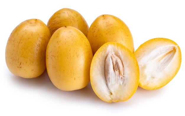 Frutta gialla fresca della palma da datteri isolata su fondo bianco.