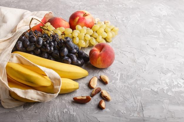Frutta in sacchetto bianco riutilizzabile in tessuto di cotone su cemento grigio. shopping, stoccaggio e riciclaggio a zero sprechi. vista laterale, copyspace.