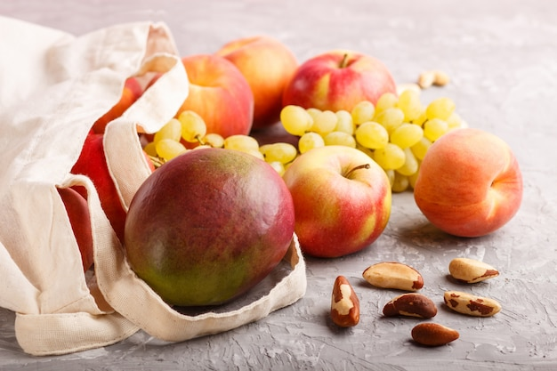Frutta in sacchetto bianco riutilizzabile in tessuto di cotone su cemento grigio. shopping, stoccaggio e riciclaggio a zero sprechi. vista laterale, da vicino.