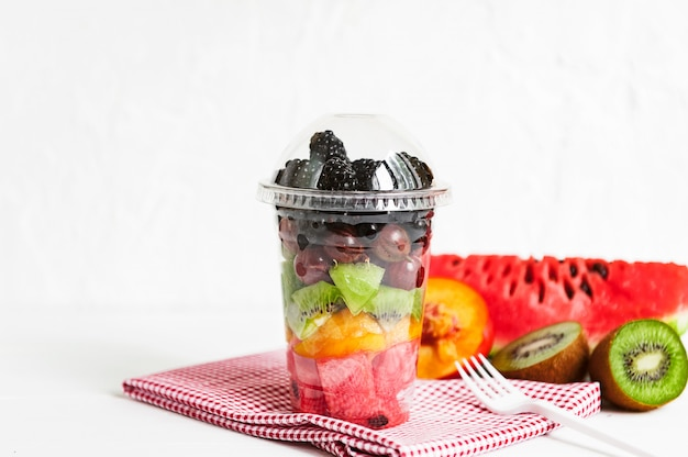 Frutta in un bicchiere di plastica.