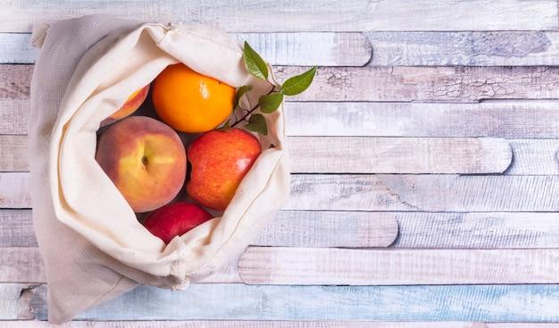 Frutta in un sacchetto di cotone eco riutilizzabile su un tavolo di legno