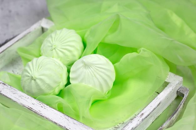 Frutta marshmallow in un vassoio di legno d'epoca su un tavolo con un panno verde