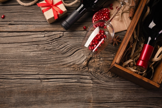 Frutta matura del melograno con un bicchiere di vino, una bottiglia e un regalo su un fondo di legno