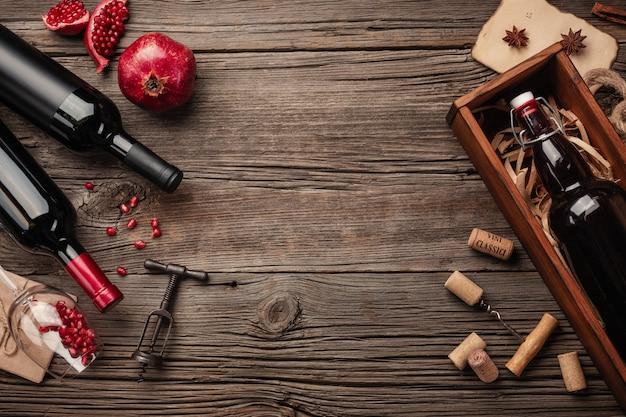 Frutta matura del melograno con un bicchiere di vino, una bottiglia in una scatola su un fondo di legno