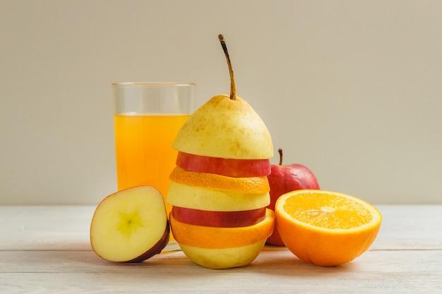 Frutta mista e succo sul tavolo di legno. concetto di cibo sano