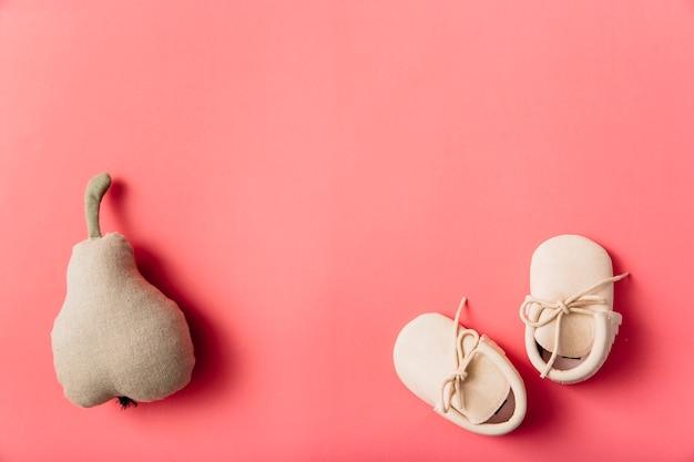 Frutta pera farcita e paio di scarpe per bambini su sfondo colorato