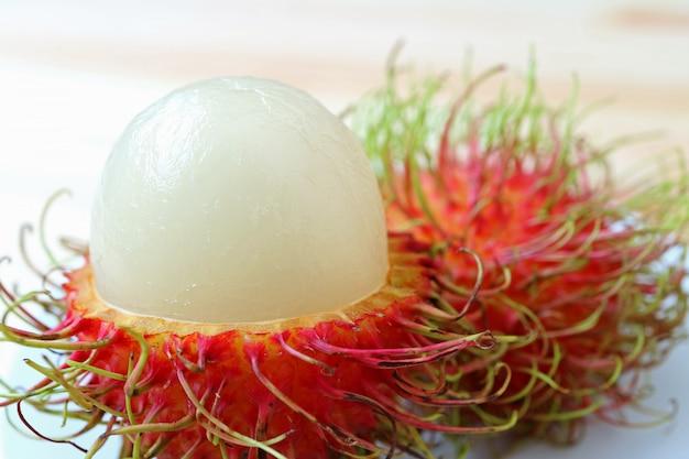 Frutta rambutan matura bianca succosa pura chiusa chiusa con buccia rossa e capelli verdi