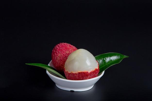 Frutta rossa del lychee disposta in un cestino.